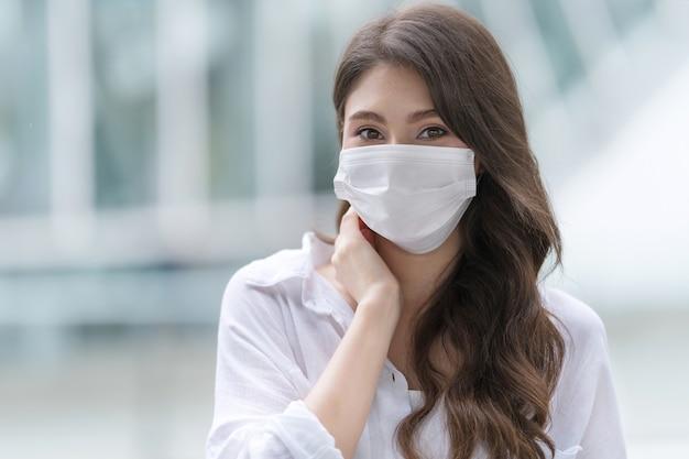 Ritratto di giovane donna che indossa la maschera medica protettiva in una città