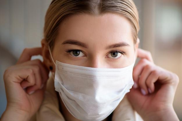 Ritratto di una giovane donna che indossa una maschera di protezione contro il coronavirus in aeroporto