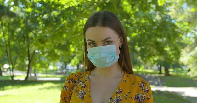 Ritratto di una giovane donna che indossa la maschera protettiva nel parco