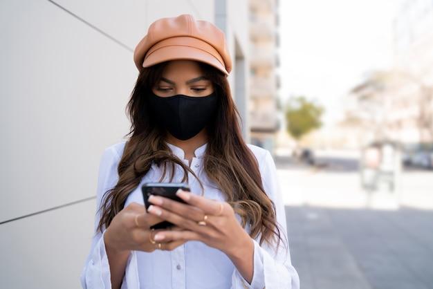 Ritratto di giovane donna che indossa la maschera protettiva e utilizzando il suo telefono cellulare in piedi all'aperto sulla strada. nuovo concetto di stile di vita normale. concetto urbano.