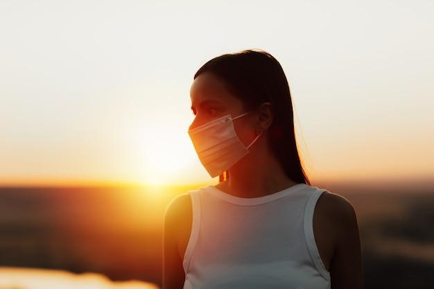 Ritratto di giovane donna che indossa la maschera medica protettiva, in piedi nel parco al tramonto arancione durante la sera d'estate.