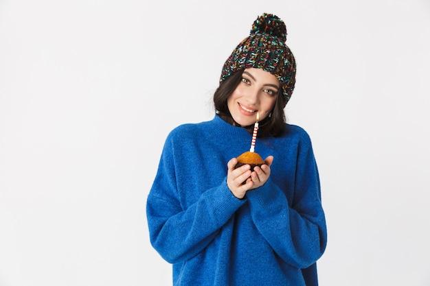 Ritratto di giovane donna che indossa il cappello invernale tenendo la torta di compleanno con una candela in piedi, isolato su bianco