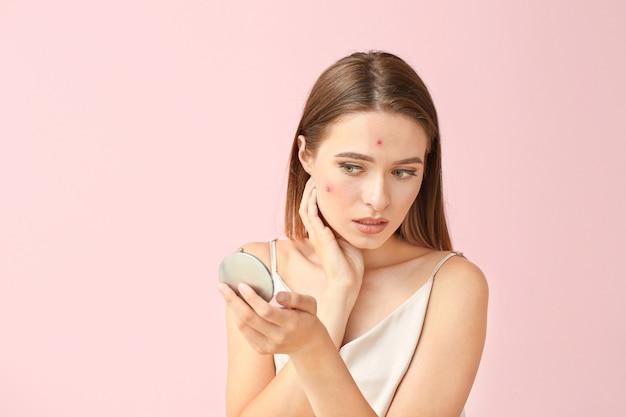 Ritratto di giovane donna con problemi di acne che si guarda allo specchio sul rosa