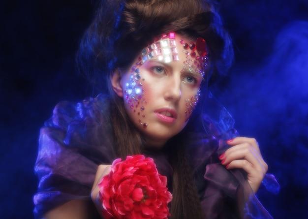 Ritratto di giovane donna con volto artistico che tiene in mano un grande fiore rosso red