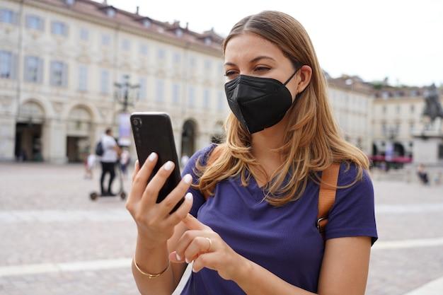 Ritratto di giovane donna con maschera protettiva nera ffp2 kn95 utilizzando il telefono cellulare con sfondo della città