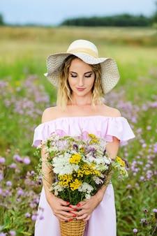 Ritratto di una giovane donna con un mazzo di fiori di campo. una ragazza con un cappello di paglia si trova in un prato fiorito.