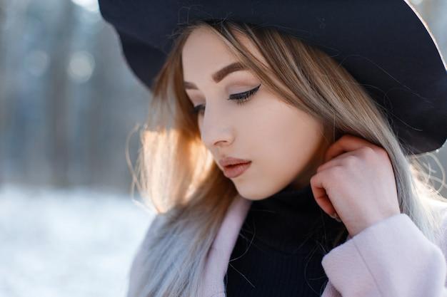 Ritratto di una giovane donna con gli occhi marroni con labbra sexy con capelli biondi con un bel trucco in un elegante cappello nero