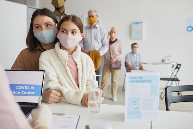Ritratto di giovane donna con bambino in attesa in fila per registrarsi per il vaccino contro il covid al centro di vaccinazione, copia spazio