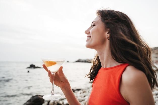 Ritratto di giovane donna con bicchiere da cocktail agghiacciante su una spiaggia