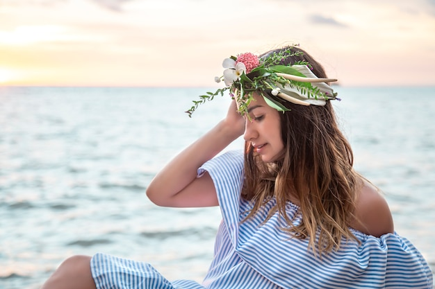 Ritratto di una giovane donna con una composizione di fiori sulla sua testa in riva al mare al tramonto.