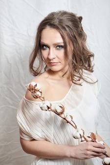 Ritratto di giovane donna con pianta di cotone con soffici fiori su bianco
