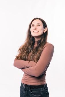 Ritratto di giovane donna con le braccia incrociate su sfondo bianco