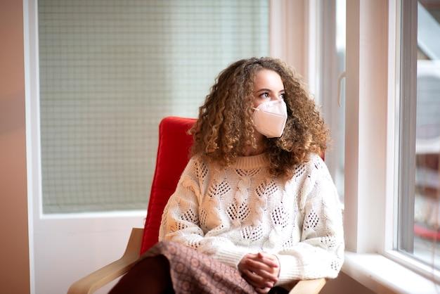 Ritratto di giovane donna con capelli ricci e occhi tristi nella mascherina protettiva medica di colore bianco che si siede alla finestra