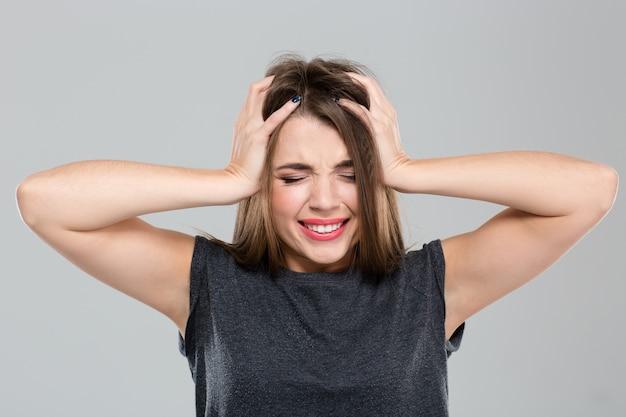 Ritratto di una giovane donna con espressione depressa in piedi isolata su uno sfondo bianco
