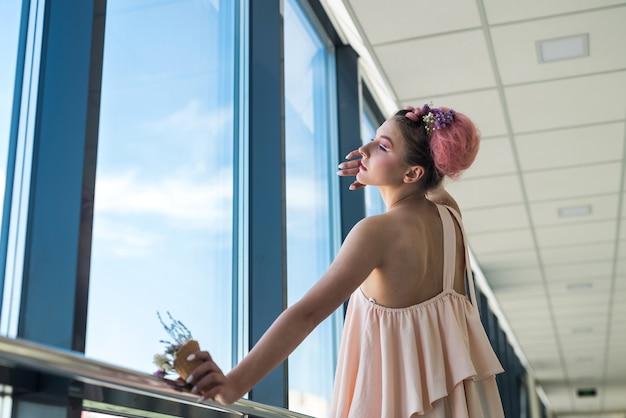 Ritratto di giovane donna con trucco di moda vicino alla finestra