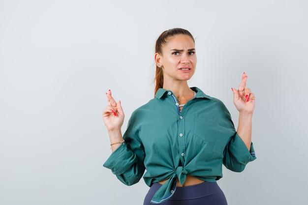 Ritratto di giovane donna con le dita incrociate in camicia verde e guardando la vista frontale ansiosa