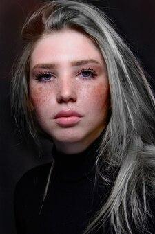 Ritratto di giovane donna con lentiggini sul viso