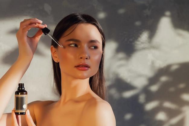 Ritratto di giovane donna con una pelle fresca e perfetta in posa sul vecchio fondo del muro con ombra dal fogliame. cosmetologia e concetto di trattamento. concetti pubblicitari di stile di vita sano, spa e cura di sé