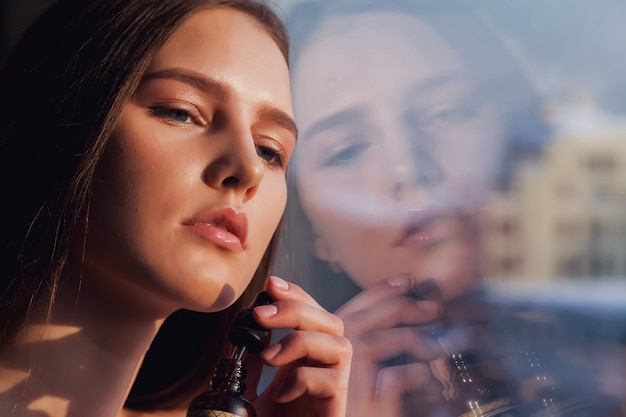 Ritratto di giovane donna con pelle fresca perfetta in posa alla finestra con riflesso nel vetro. cosmetologia e concetto di trattamento. concetti pubblicitari di stile di vita sano, spa e cura di sé. copia spazio