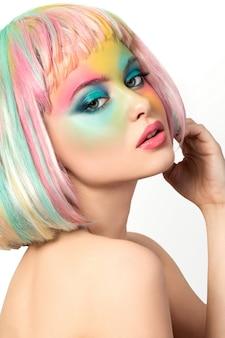 Ritratto di giovane donna con trucco colorato arcobaleno divertente che tocca i suoi capelli