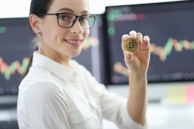 Ritratto di giovane donna con gli occhiali che tengono bitcoin sullo sfondo di indicatori finanziari