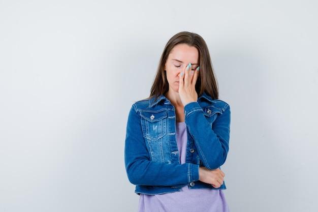Ritratto di giovane donna con la mano sul viso in giacca di jeans e guardando la vista frontale angosciata
