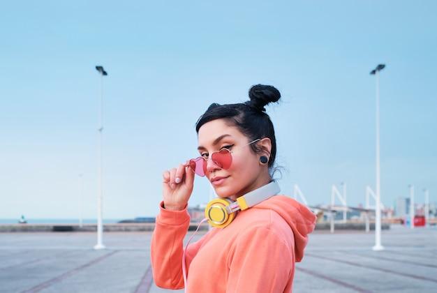 Ritratto di giovane donna con occhiali da sole a forma di cuore