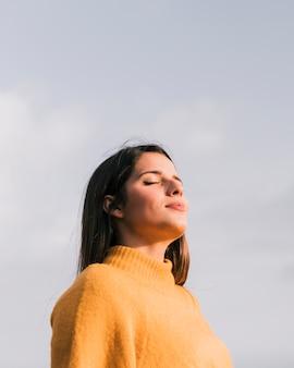 Ritratto di una giovane donna con i suoi occhi chiusi in piedi contro il cielo blu