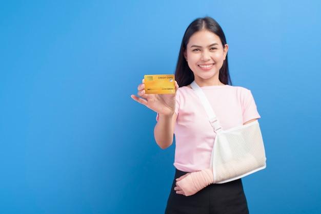 Un ritratto di giovane donna con un braccio ferito in una imbracatura in possesso di una carta di credito o di una tessera di assicurazione medica su sfondo blu in studio, assicurazione e concetto di assistenza sanitaria