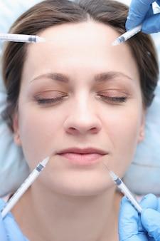 Ritratto di giovane donna con molte siringhe vicino al viso