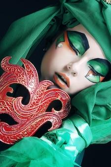 Ritratto di giovane donna con maschera in un'immagine teatrale creativa.