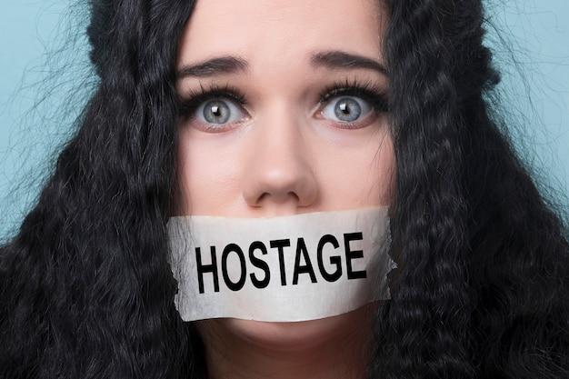 Ritratto di giovane donna con la bocca e le labbra sigillate nel nastro adesivo trattenuto e abusato censurato e vietato di parlare, concetto di ostaggio