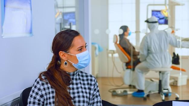 Ritratto di giovane donna con maschera di protezione che discute seduti su sedie mantenendo la distanza sociale in clinica stomatologica, in attesa del medico durante il coronavirus. concetto di nuova normale visita dal dentista