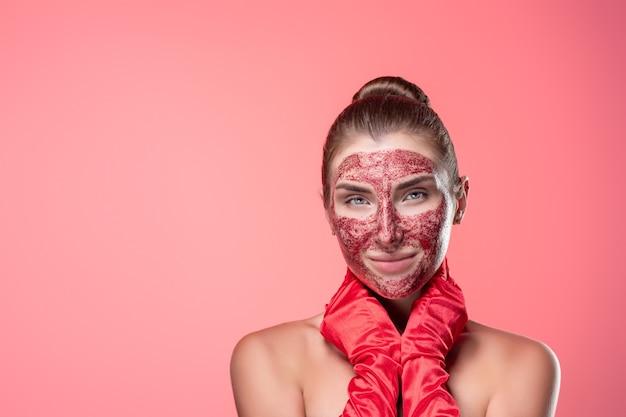 Ritratto di una giovane donna con una maschera cosmetica rossa sul viso in guanti rossi