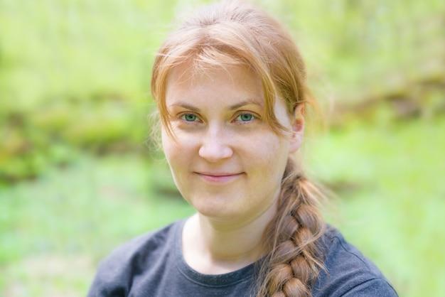 Ritratto di giovane donna con capelli rossi e treccia nella foresta verde