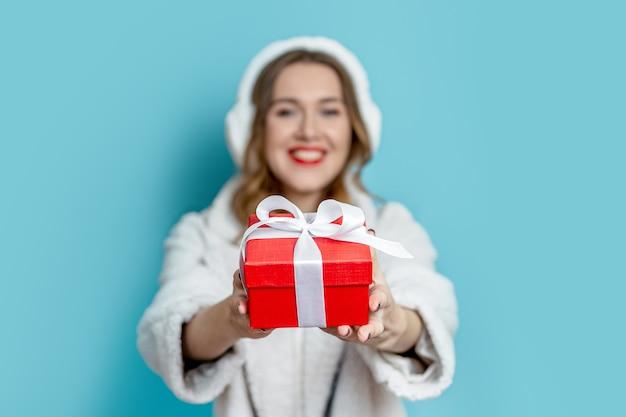 Ritratto di una giovane donna con labbra rosse che indossa un cappotto di pelliccia bianca artificiale