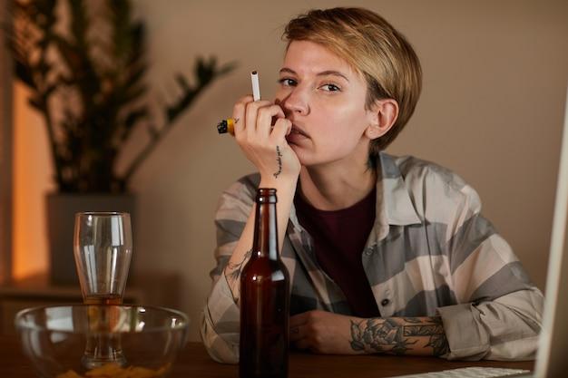 Ritratto di giovane donna con i capelli corti seduto al tavolo con birra e tenendo la sigaretta e guardando la fotocamera