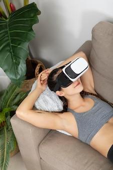Giovane donna del ritratto con la cuffia avricolare di realtà virtuale