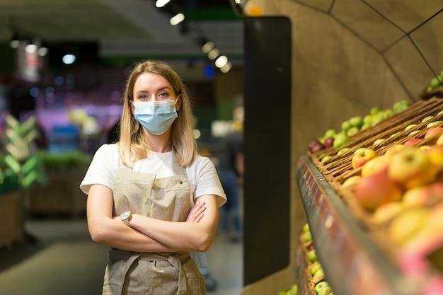 Ritratto di giovane lavoratrice venditore in un supermercato di sezione vegetale in piedi in una maschera facciale protetta con le braccia incrociate. fruttivendolo femmina che guarda l'obbiettivo nel mercato del negozio di frutta dipendente in un grembiule da lavoro
