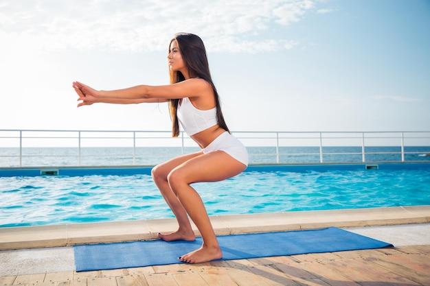 Ritratto di una giovane donna che lavora sul materassino yoga all'aperto al mattino