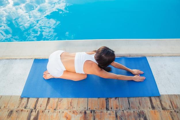 Ritratto di una giovane donna che lavora sul materassino yoga all'aperto