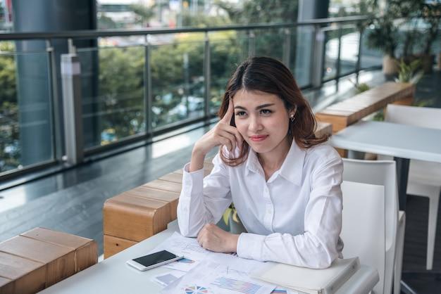 Ritratti di bella donna asiatica nell'espressione di pensiero con documento nel lavoro.