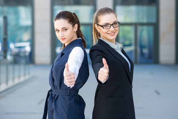 Ritratti di belle giovani donne d'affari di successo che mostrano i pollici in su