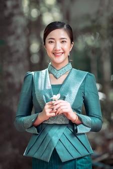 Ritratti, belle donne in costume nazionale del laos in piedi con fiori in champa, che è il fiore nazionale del laos