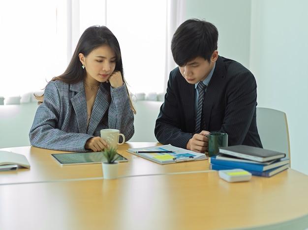 Ritratti di uomini d'affari che hanno una conversazione seria mentre si consultano sul loro lavoro in sala riunioni