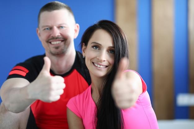 Ritratti di uomo e donna sorridenti in palestra e mostrando il pollice in alto gesto