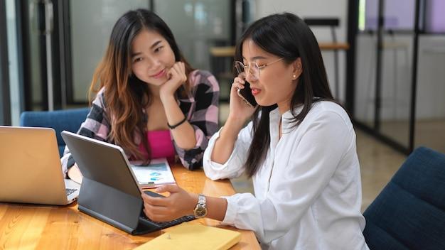 Ritratti di due studentesse che svolgono insieme compiti di gruppo