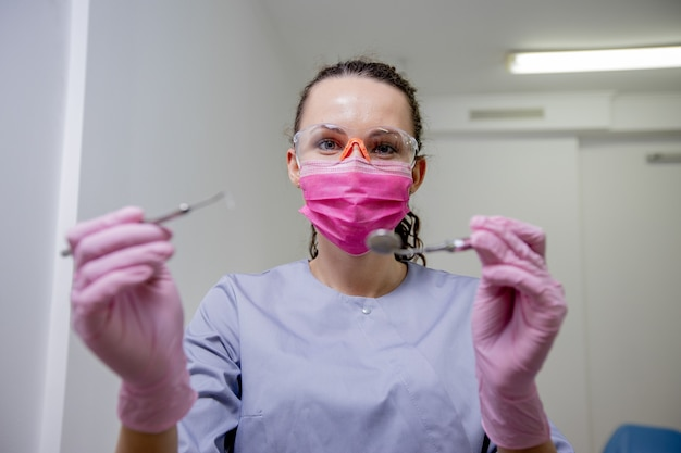 Ritratti di una donna di dentista di professione di aspetto caucasico con strumenti in mano, concetto di medicina.