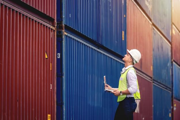 L'ingegnere operaio di portrit tiene in mano un laptop e cammina per controllare la scatola dei container dalla nave da carico per l'esportazione e l'importazione