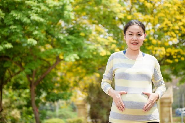 Porttrait della donna asiatica incinta che sorride, con uno sfondo naturale.